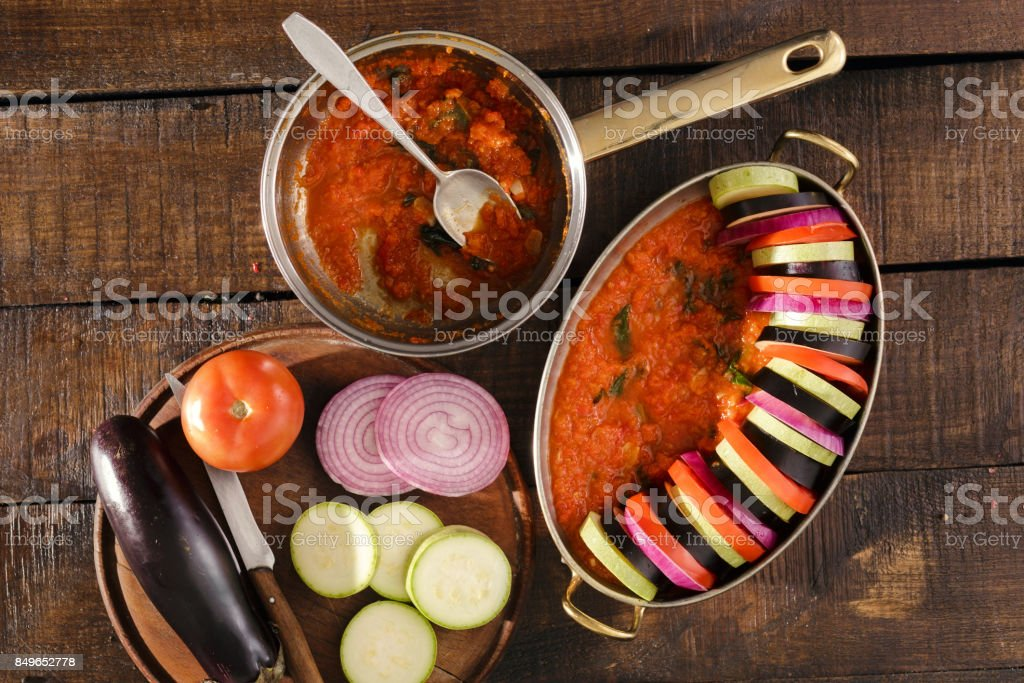 Ingredients for cooking vegetarian dish ratatouille on a wooden table stock photo