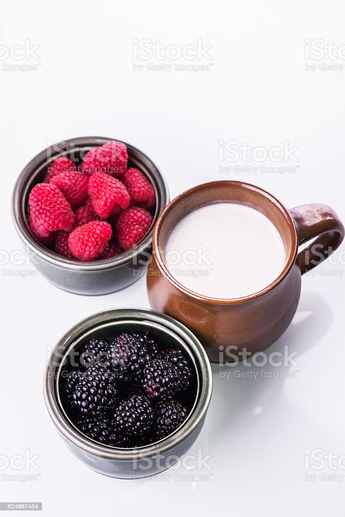 Ingredients for milkshake: fresh raspberries, blackberries and milk stock photo