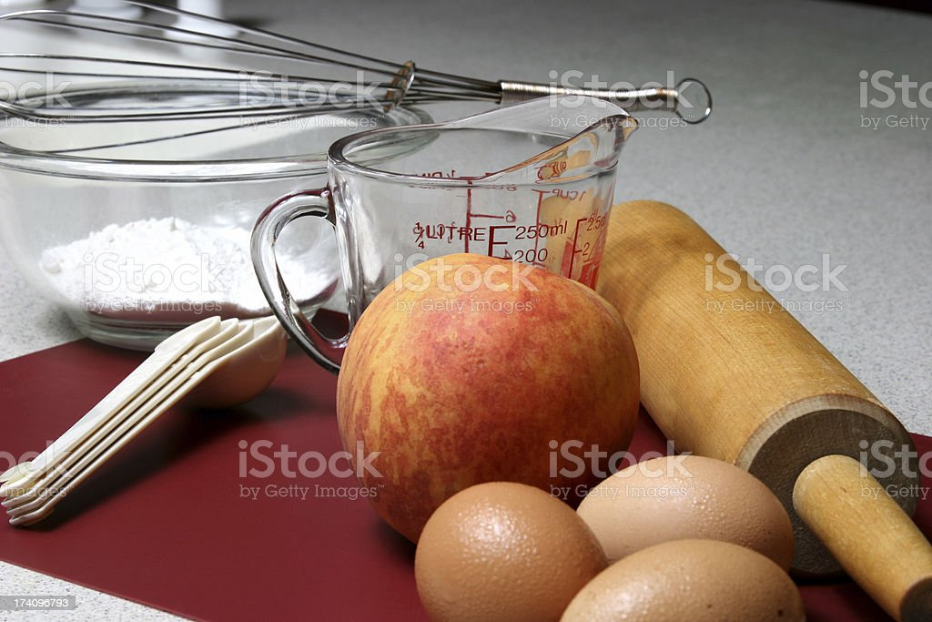 Ingredients for peach cobbler. Eggs, flour, measuring cup, rolling pin. royalty-free stock photo