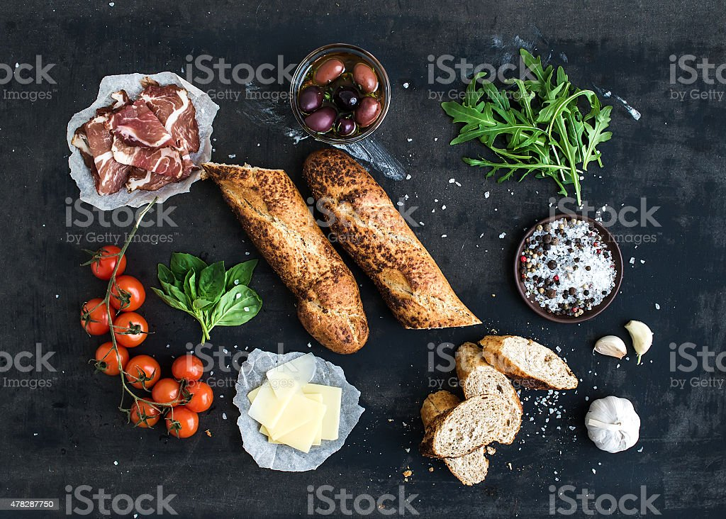 Ingredients for sandwich with smoked meat, baguette, basil, arugula, olives stock photo