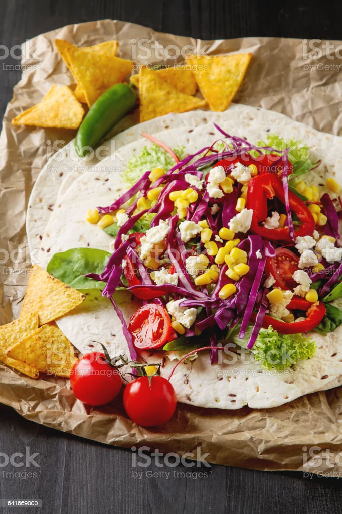 Ingredients for tacos or burrito making. Fresh organic vegetables and tortillas on rustic background, top view, stock photo