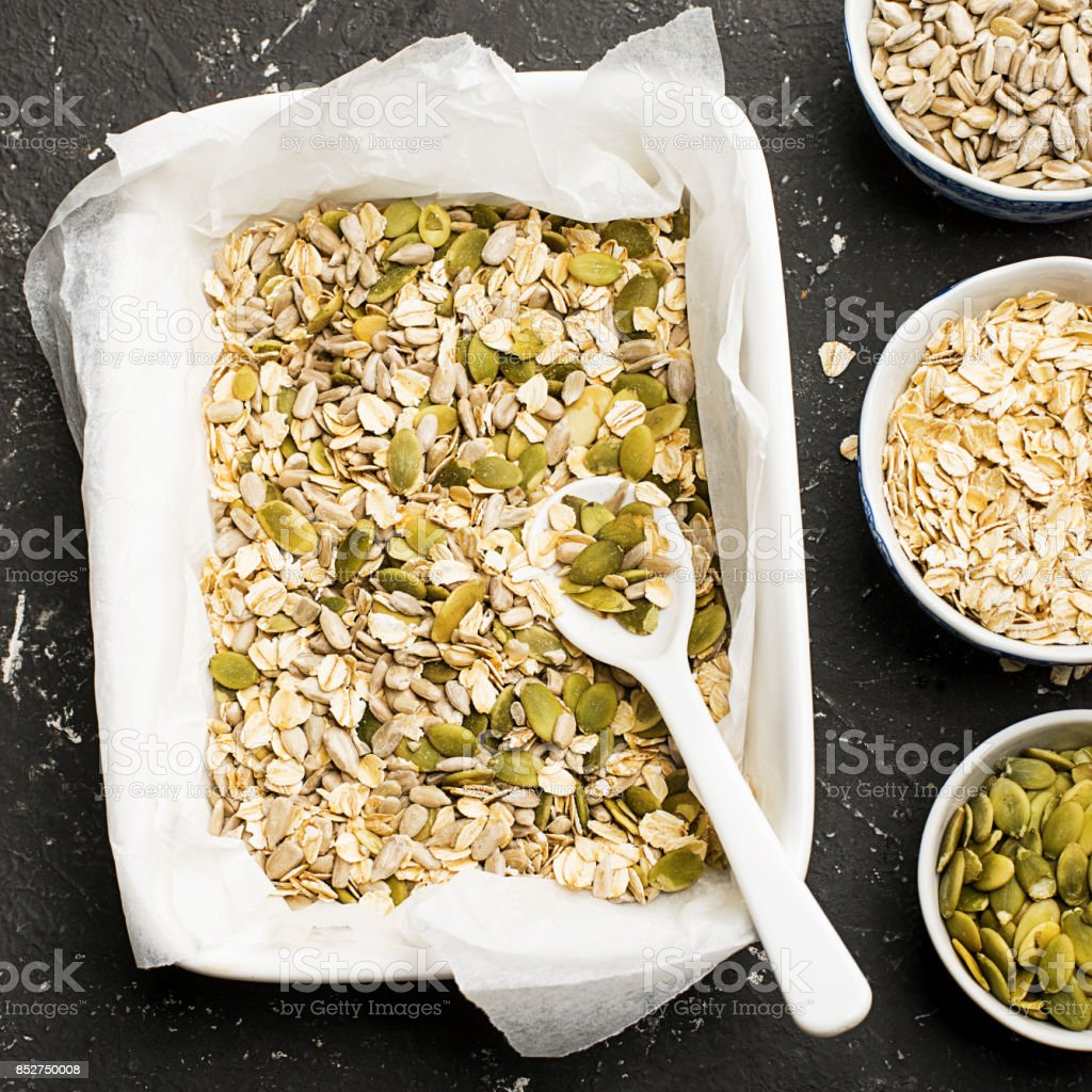 Ingredients for the preparation of baked crispy appetizing toping for thick autumn winter vegetable soups puree from pumpkin seeds, sunflower seeds, oat flakes in ceramic form on a dark background. Top View. stock photo