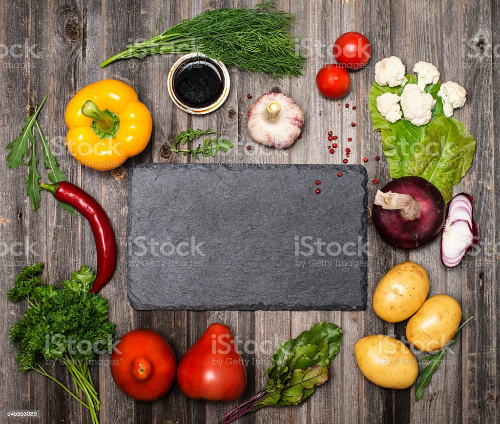Ingredients for vegetarian cooking around slate board. stock photo