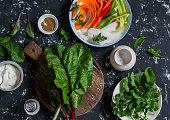 Ingredients to prepare vegetable rolls on dark background