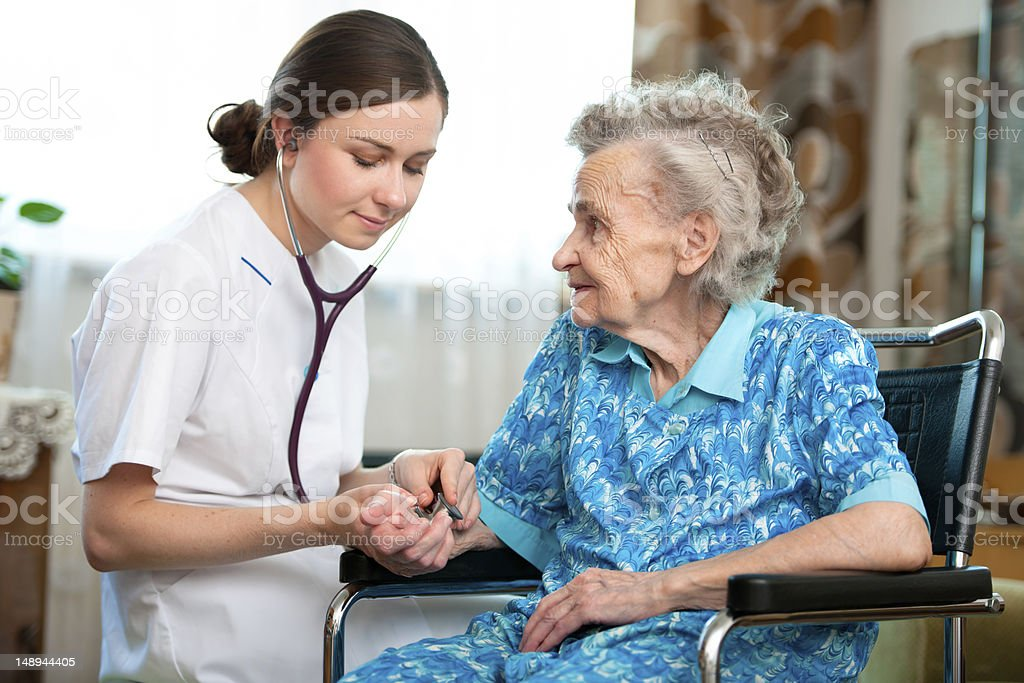 In-home nurse helping an elderly woman royalty-free stock photo