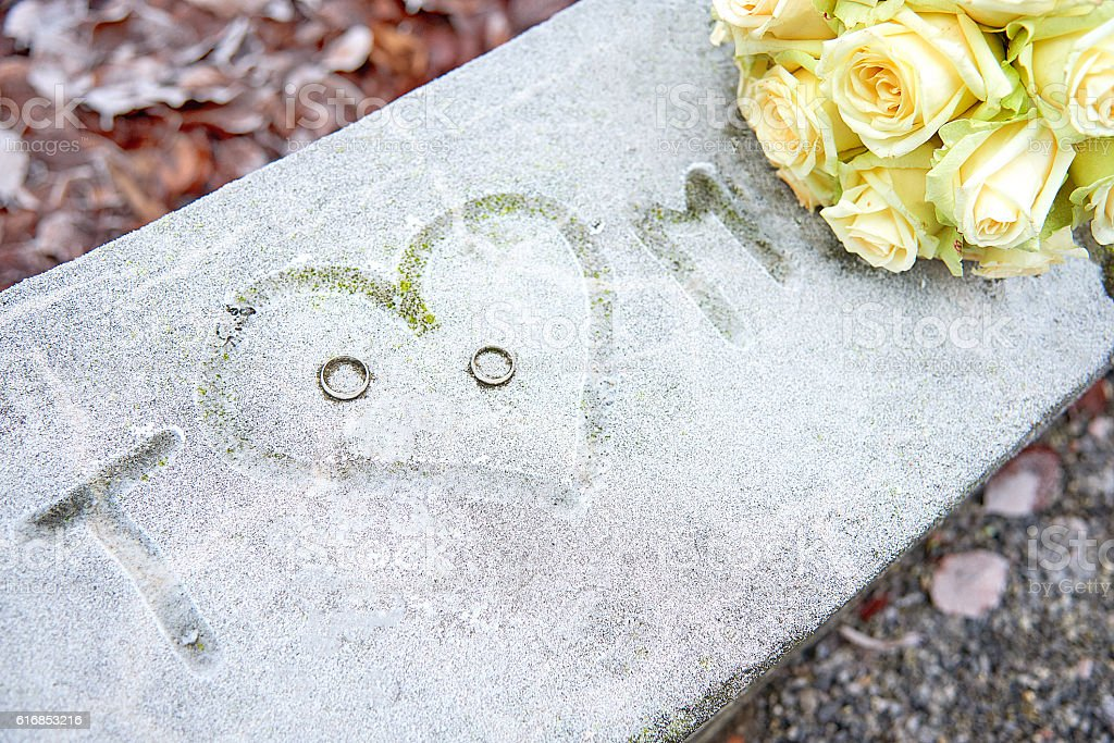 Initials, wedding rings and white roses on a frozen surface stock photo