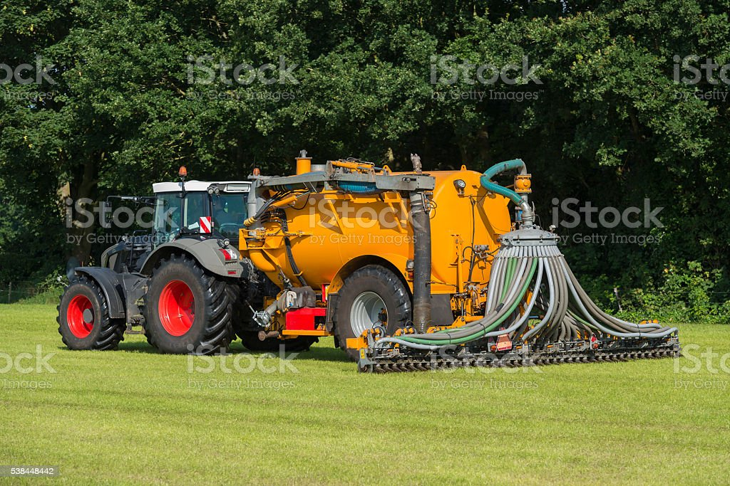 injecting manure in a pasture stock photo