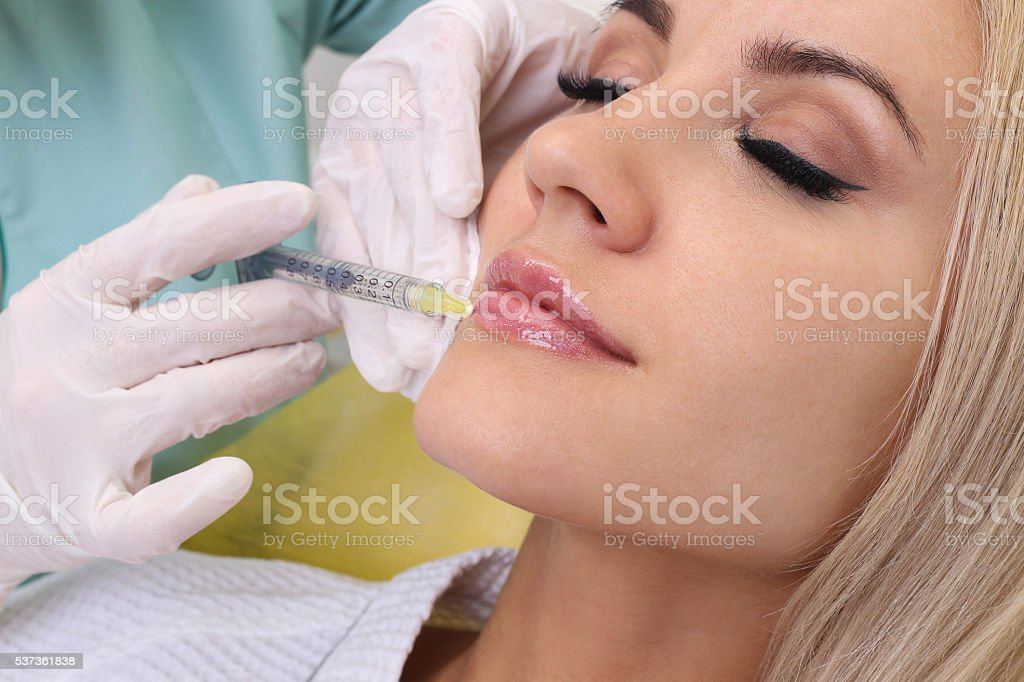 Injection in her lips. stock photo