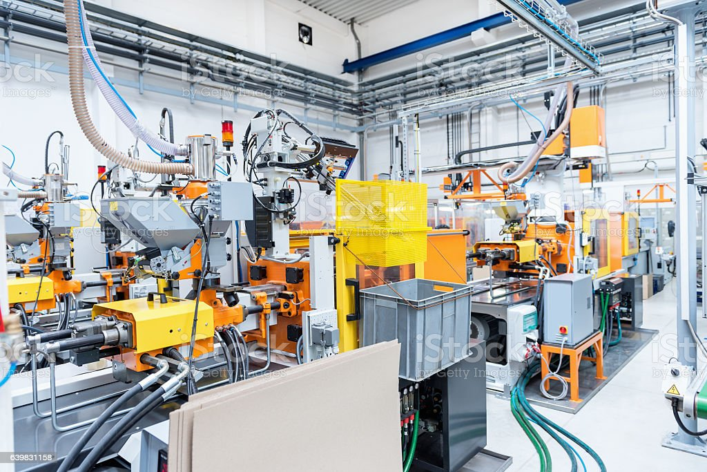 Injection moulding machines inside of plastic factory stock photo