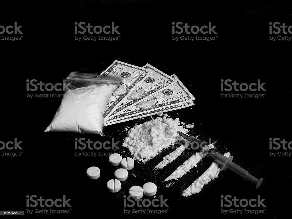 Injection syringe on cocaine, pills and dollar bills stock photo