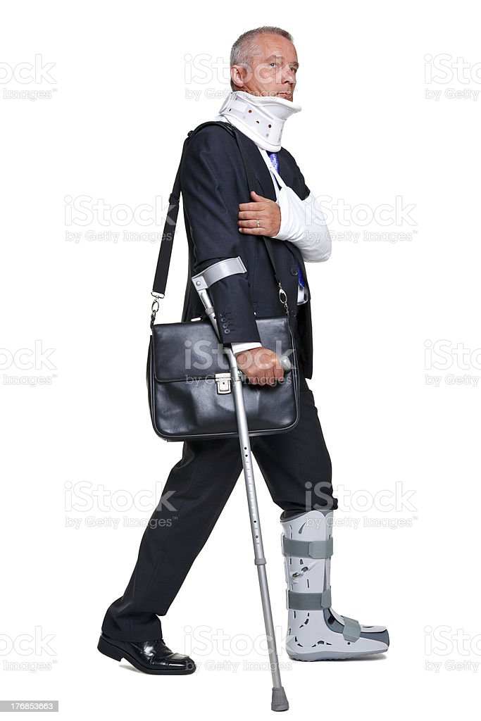 Injred businessman walking with crutch isolated on white royalty-free stock photo