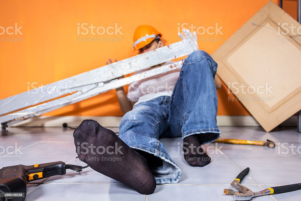 Injured construction worker laying on floor with orange wall stock photo