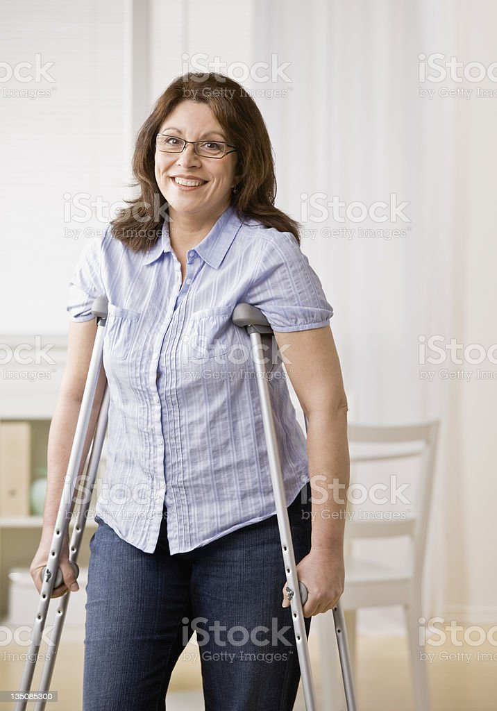 Injured disabled woman using crutches to walk stock photo