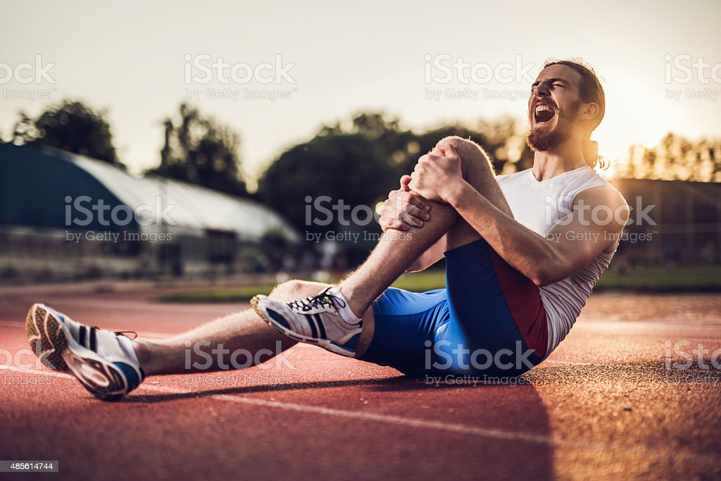 Injured male athlete screaming in pain at sunset. stock photo