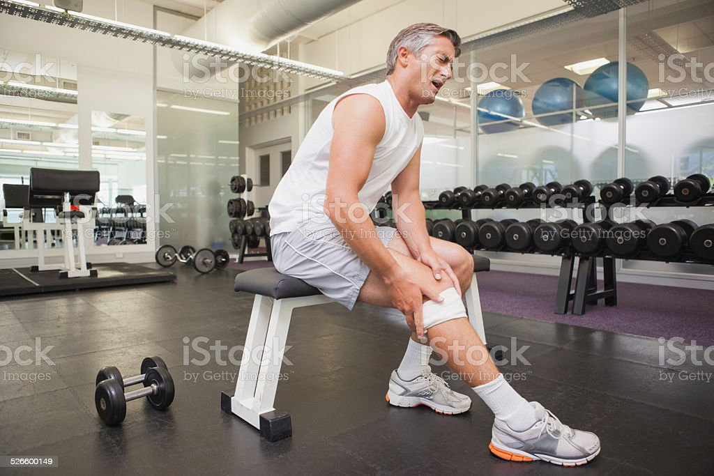 Injured man gripping his knee in the weights room stock photo