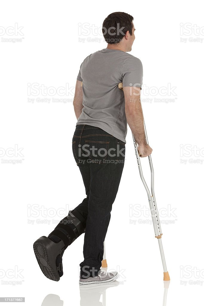 Injured man jumping with the help of crutches royalty-free stock photo