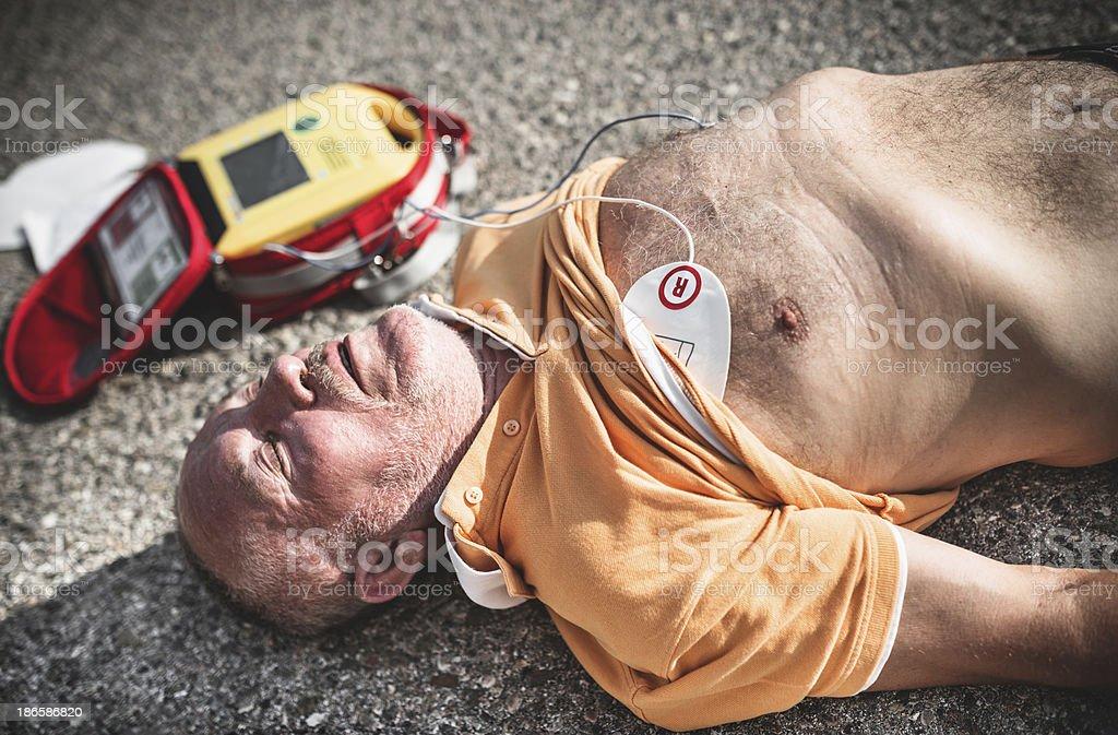 injured man on the asphalt with defribillator royalty-free stock photo