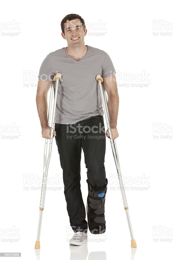 Injured man walking with the help of crutches royalty-free stock photo