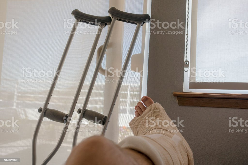 Injured Person With Sprained or Broken Ankle Foot Crutches stock photo