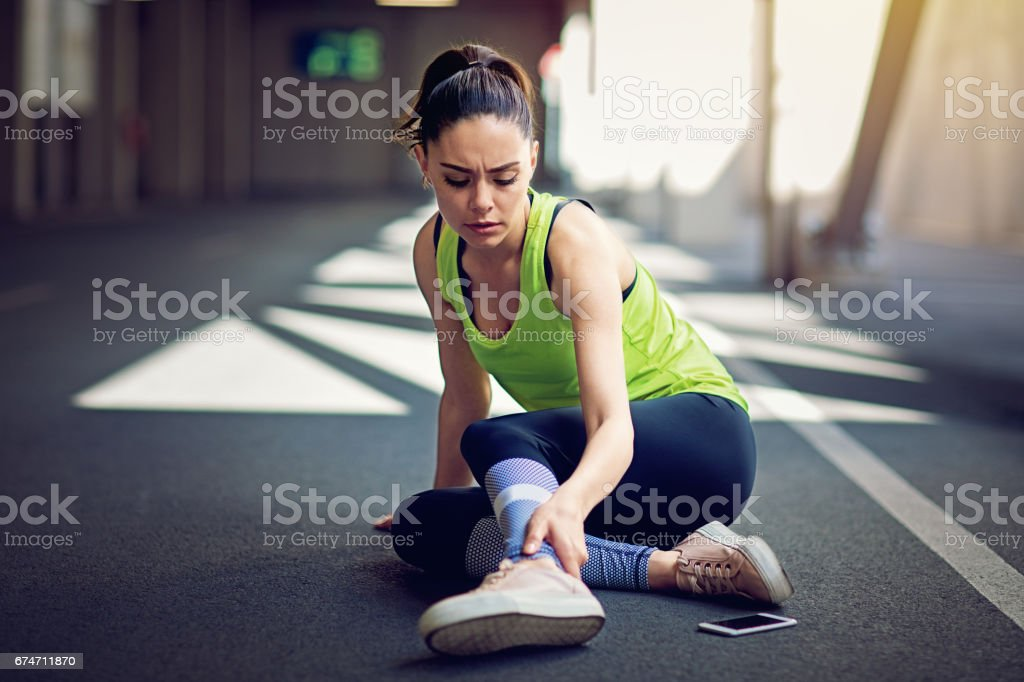 Injured runner sitting on the ground with broken mobile phone stock photo