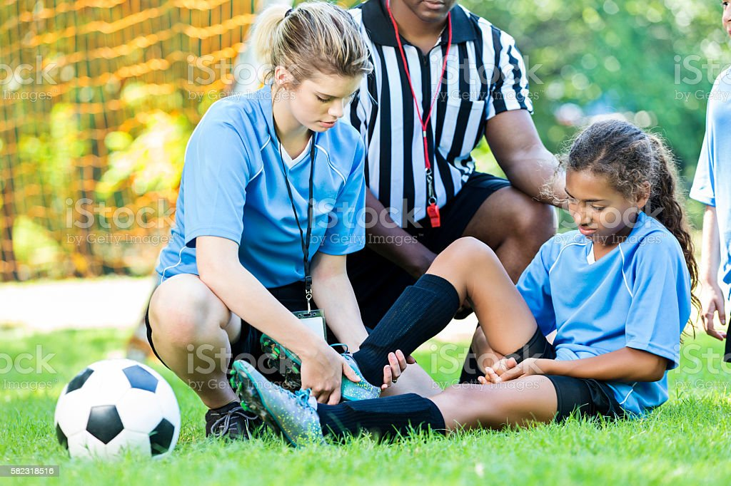 Injured soccer player getting her ankle checked by her coach stock photo