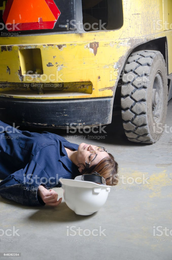 Injured woman worker on floor in front of vehicle stock photo