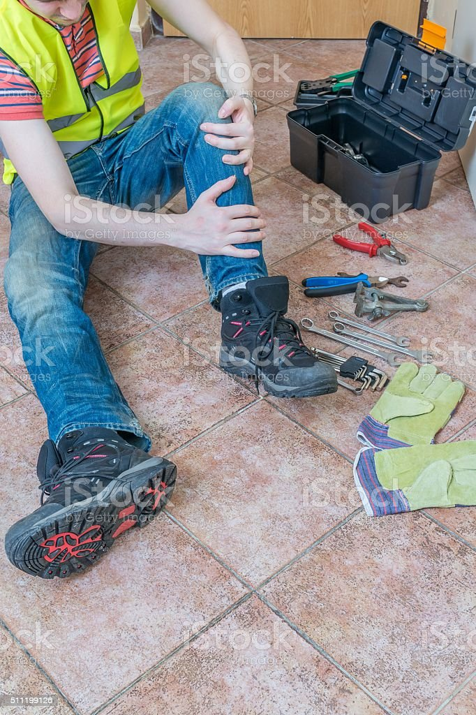 Injured worker had accident. Injured leg or knee. stock photo