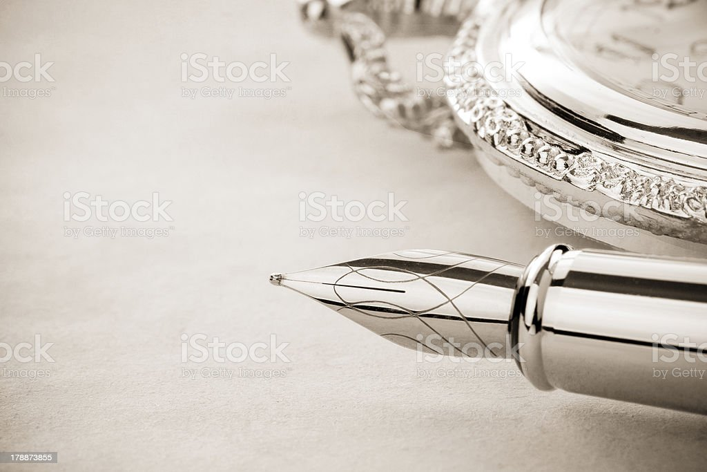 ink pen and watch on parchment royalty-free stock photo