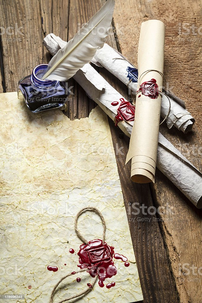 Inkwell and ancient scrolls on wooden table royalty-free stock photo