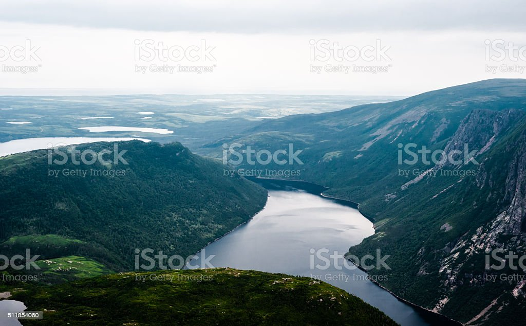 Inland fjord between steep cliffs against green landscape stock photo