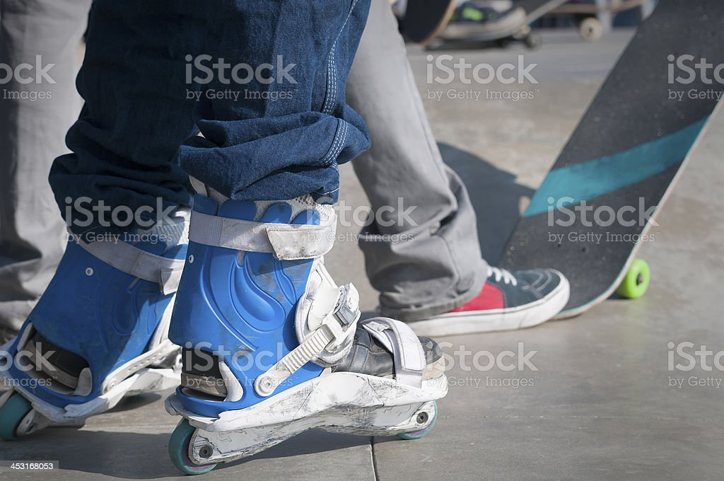 Inline Skater and Skaterboarder at Skate Park royalty-free stock photo