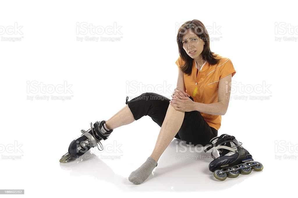Inline skater sits injured on the ground royalty-free stock photo