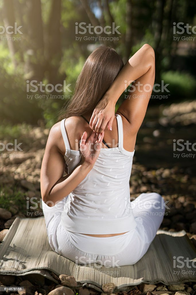 Rear view of a beautiful caucasian woman doing yoga and meditation in...