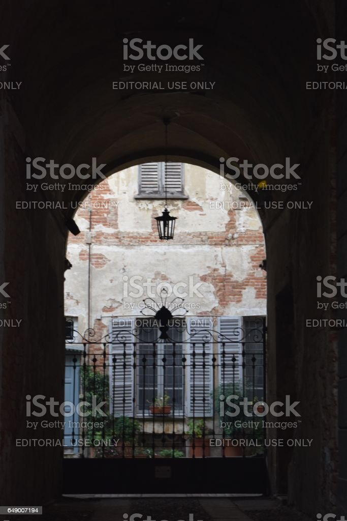 Inner courtyard of an ancient building. (Seen through a  wrought iron gate) stock photo