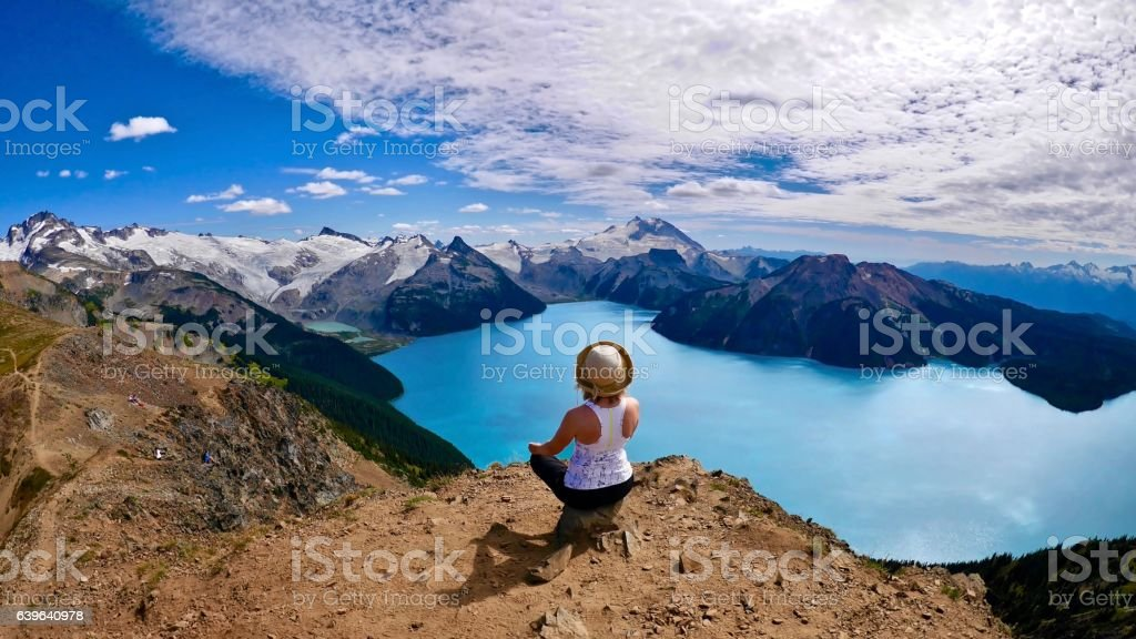 Inner peace. Woaman doing yoga above alpine lake. stock photo
