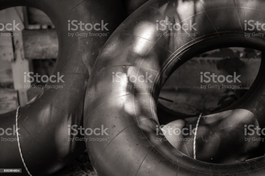 Inner tubes along a fence stock photo