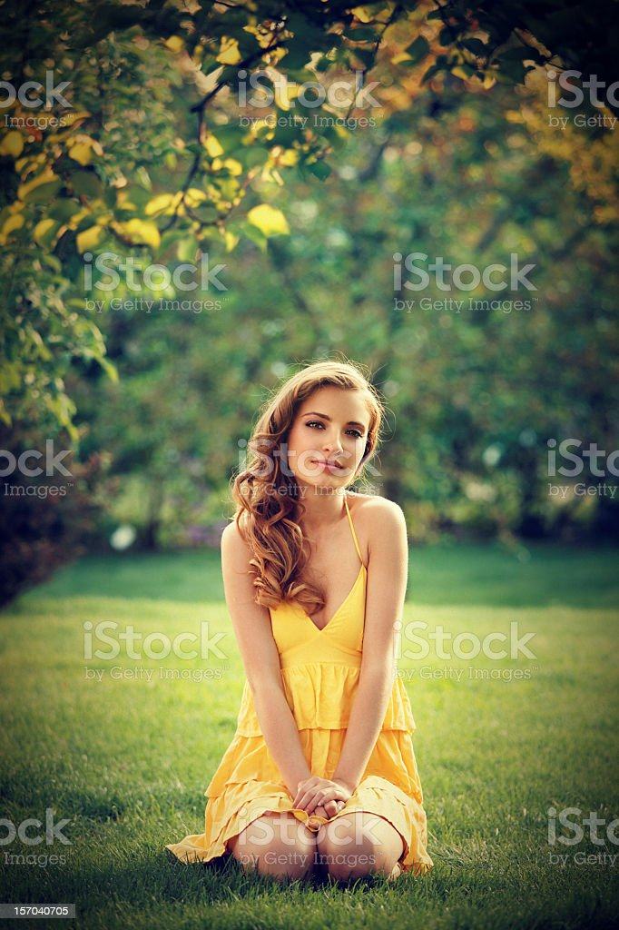 innocence - beautiful girl kneeling on the grass royalty-free stock photo