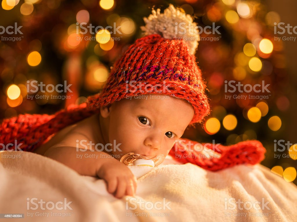 Innocent baby relaxing on a blanket during Christmas time. stock photo