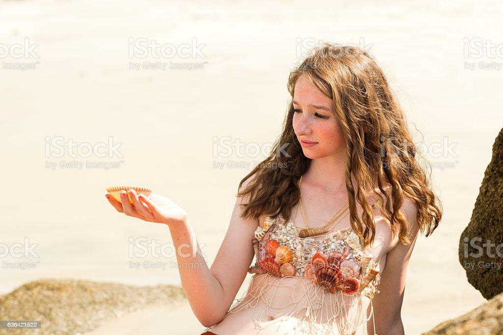 innocent girl with seashell at beach stock photo