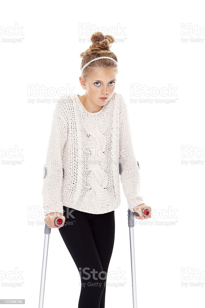 Innocent young girl on crutches looking at you royalty-free stock photo