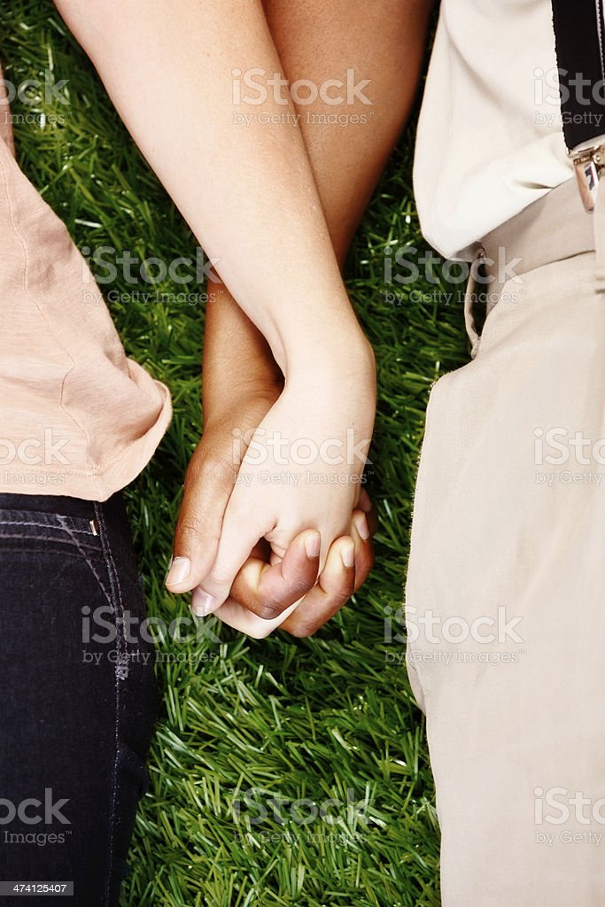 Innocent young love; holding hands on grass stock photo