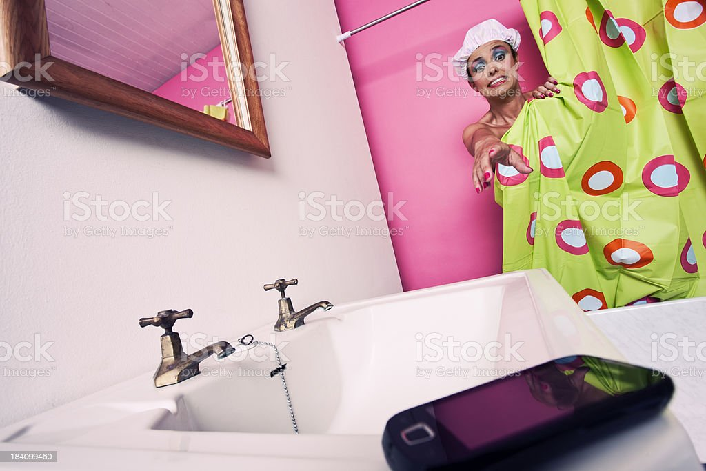 One young woman reaching out from behind the shower curtain for the...