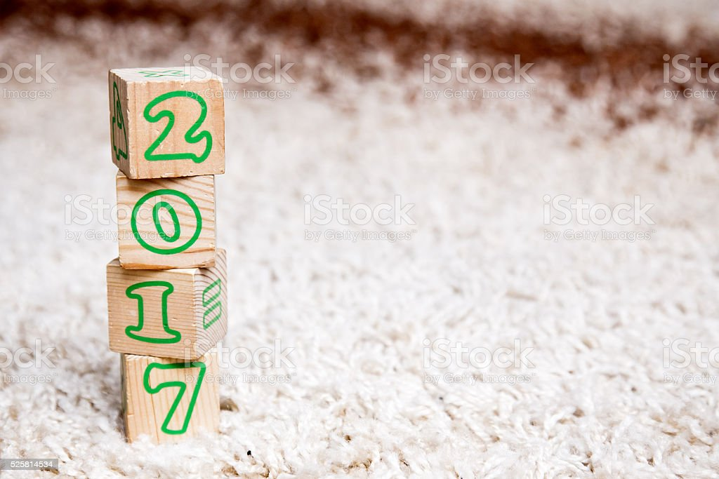inscription 2017 made of wooden cubes lying on terry carpet stock photo