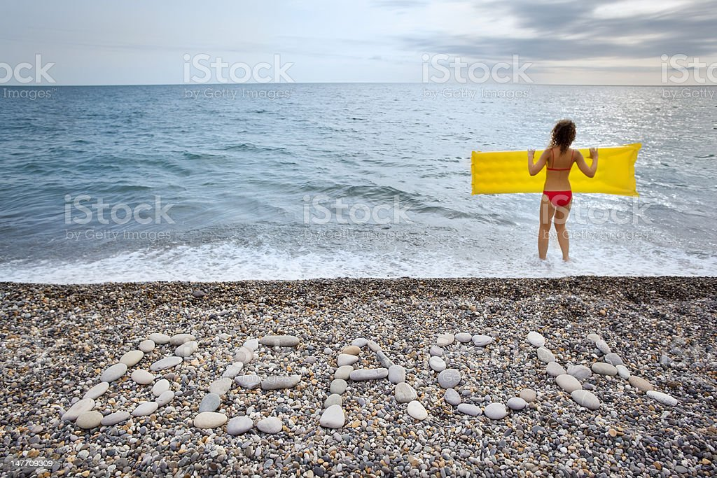 Inscription from stones BEACH at coast and woman with mattress royalty-free stock photo