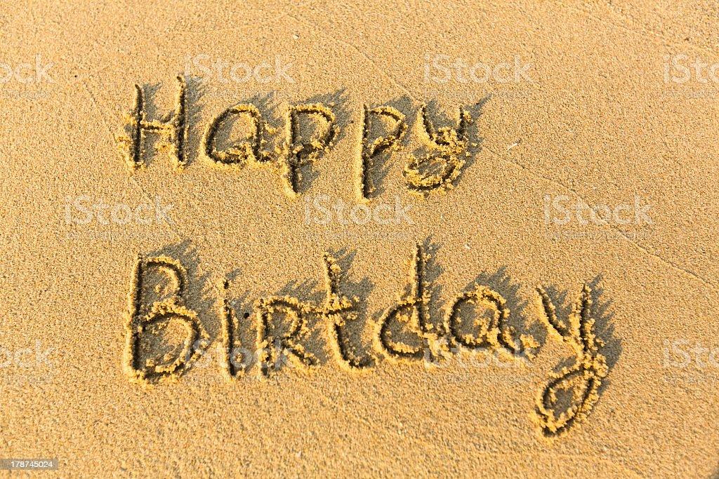 Inscription Happy Birthday on texture of sand. stock photo