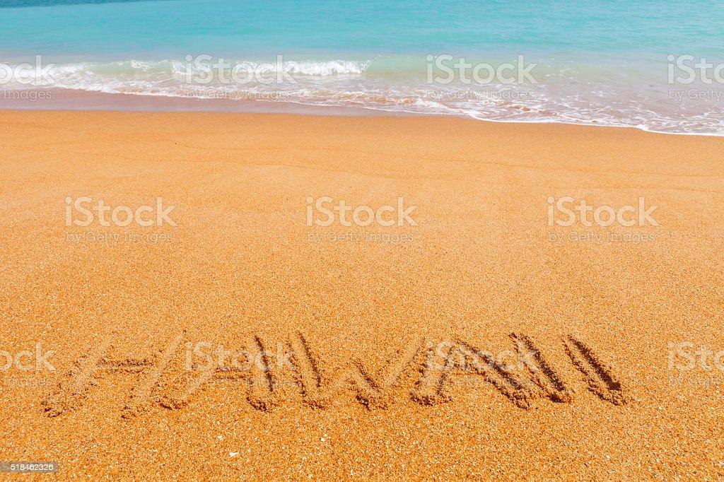 Inscription 'Hawaii' made on beautiful beach by blue sea stock photo