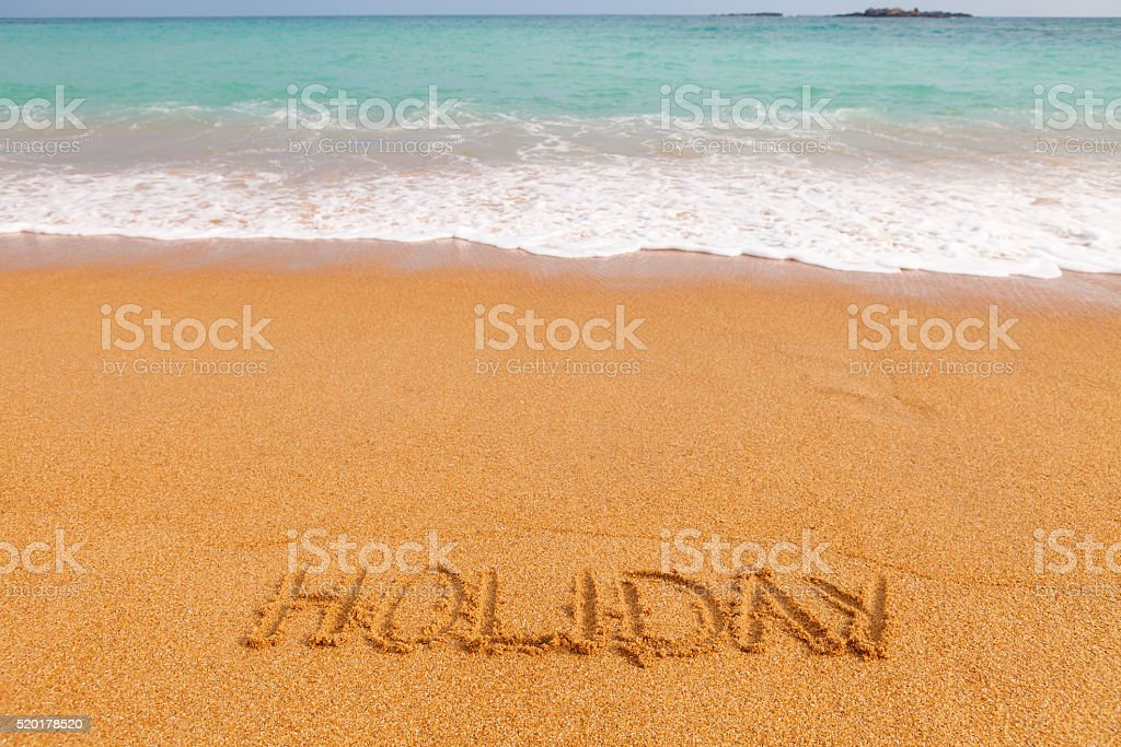 Inscription HOLIDAY made on beautiful beach by the blue sea stock photo
