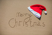 inscription on the wet sand and cap of Santa Claus
