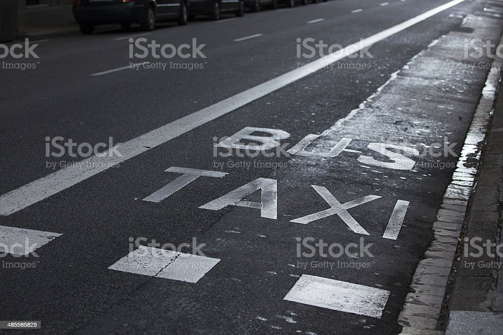 Inscriptions taxi and bus on the roadway royalty-free stock photo