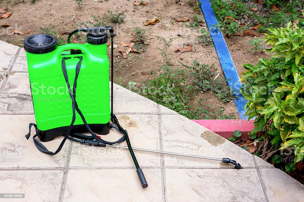 Insecticide sprayer isolated on the floor in the garden stock photo